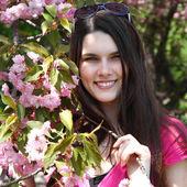 若い美女の近く咲く春の庭の桜の木 — ストック写真