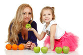 Mother with liitle daughter with apples and oranges — Stock Photo