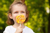 Happy little girl with sweet candy nature outdoor — Stock Photo