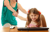Girl with internet dependence playing with keyboard being dragged by mother from her computer — Stock Photo
