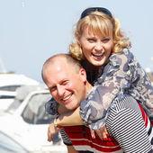 Happy attractive mid adult couple have fun piggyback outdoor — Stock Photo