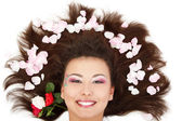 Beautiful female head with long brunet hair and rose petal — Stock Photo