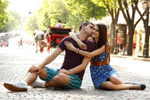 Love story of young couple sitting on stone paving hug and kiss — Foto Stock