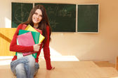 Beautiful teen girl high achiever in classroom near desk happy smiling — ストック写真