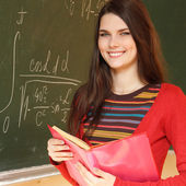 Beautiful teen girl high achiever in classroom near desk with formulas of higher mathematics — 图库照片