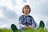 Happy little boy sitting on green grass — Stock Photo