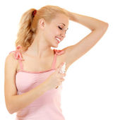 Young woman putting deoporant on her armpit — Stock Photo