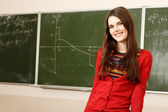Beautiful teen girl high achiever in classroom near desk happy smiling — Stok fotoğraf