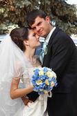 Beautiful young bride hugs groom in love — Stock Photo