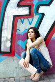 Beautiful fashion girl sitting near wall — Stock Photo