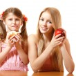 图库照片: Teeny girl with red apple and little girl with cake