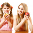 Foto Stock: Teeny girl with red apple and little girl with cake