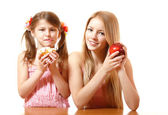 Teeny girl with red apple and little girl with cake — Stock Photo