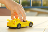 Boy play with a car — Stockfoto