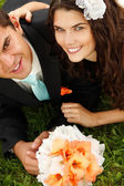 Young bride and groom lying on green grass — Stock Photo