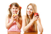 Teeny girl with red apple and little girl with cake — Stok fotoğraf