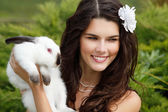 Bride smiling and holding cute rabbit — Stock Photo