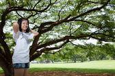 Ung kvinna som står under ett stort träd. — Stockfoto