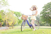 Asian woman hold bicycle on the lawn. — Stok fotoğraf