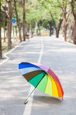Multicolored umbrella on the sidewalk. — Stock Photo