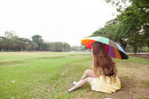 Woman with umbrella and sitting on the lawn. — Stock Photo