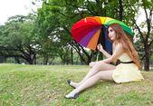 Kobieta z parasolem i siedzi na trawniku. — Zdjęcie stockowe