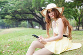 Woman sitting on grass and using a tablet. — Stock Photo