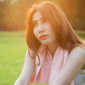 Woman sitting on lawn in park. — Stock Photo