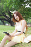 Woman sitting on lawn holding tablet. — Stock Photo