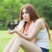 Woman sitting tired and drinking water after exercise. — Stock Photo