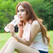 Frau sitzt müde und Trinkwasser nach dem Training. — Stockfoto