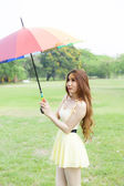 Woman with umbrella standing on the lawn. — Stock Photo