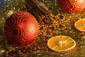 Red christmas ball, zimt, orange und perlen — Stockfoto