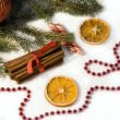 Red christmas ball, cinnamon, orange and beads — Stock Photo