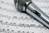 The included microphone is on the musical notation — Stockfoto