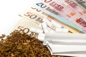 Tobacco, carbon filters, paper against the background of money — Stock Photo