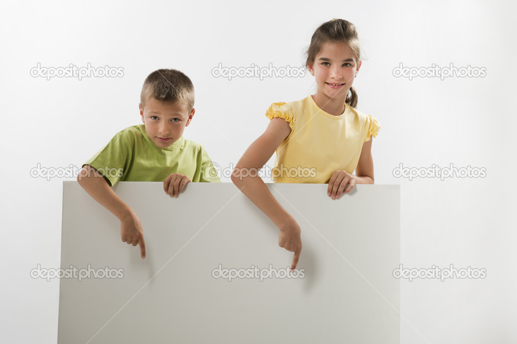 Two children holding a blank sign and looking at it, you can add your own text — Stock Photo #13996761