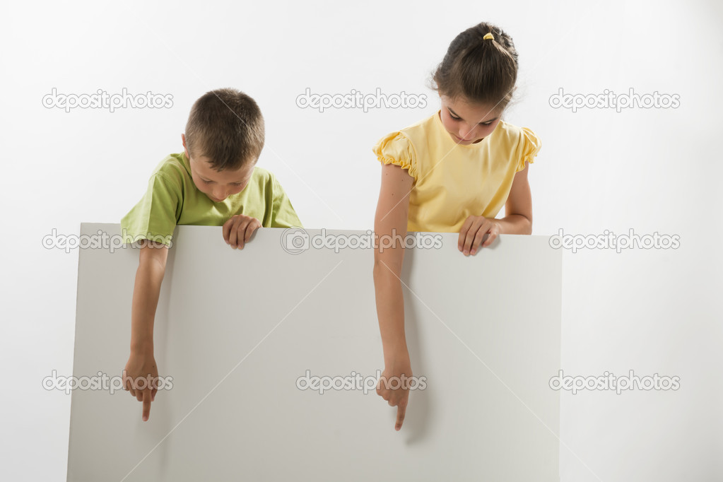 Two children holding a blank sign and looking at it, you can add your own text — Stock Photo #13996762