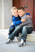 Brothers sitting on door steps — Stock Photo