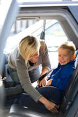 Mother fastening son's seatbelt — Stock Photo