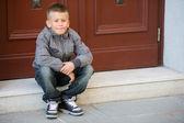 Boy sitting on steps — Stock Photo