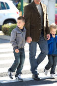 Father and sons on cross walk — Stock Photo