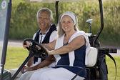 ゴルフカートに年配のカップル — ストック写真
