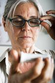 Starszy kobieta czytanie medycyny — Zdjęcie stockowe