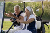 Senior couple on the golf cart — Stock Photo