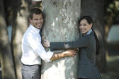 Businesspeople outdoor hugging a tree — Стоковое фото