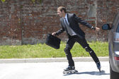 Businessman parking his car and rollerblading — Stock Photo