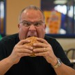 Man eating burger in fast food restaurant — Stock Photo #10476774