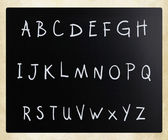 Text handwritten with white chalk on a blackboard — Stock fotografie