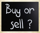 """Buy or sell"" handwritten with white chalk on a blackboard — Stockfoto"
